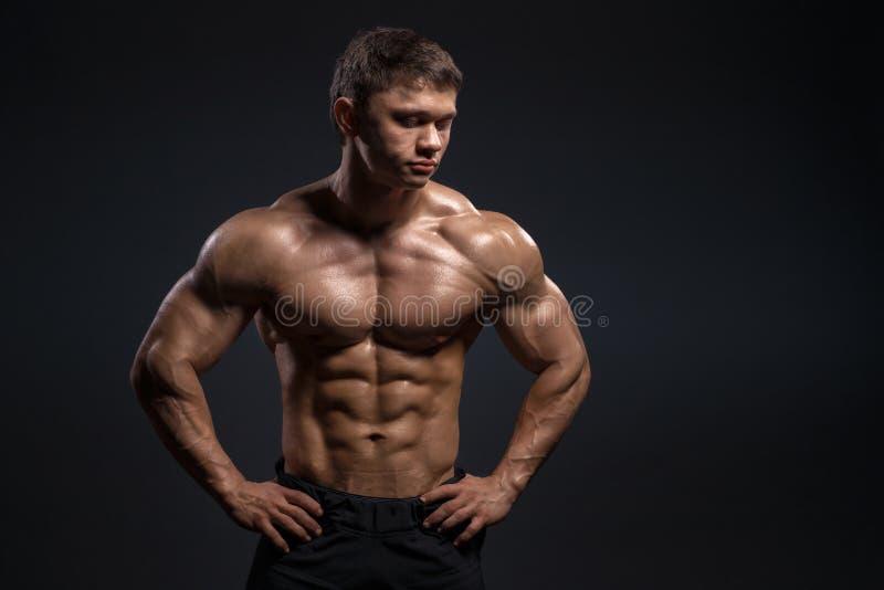 Przystojny mięśniowy bodybuilder pozuje nad czarnym tłem zdjęcia royalty free