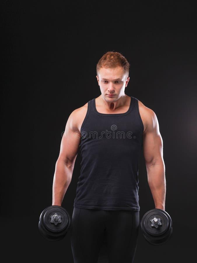 Przystojny mięśniowy mężczyzna pracujący z dumbbells out fotografia stock
