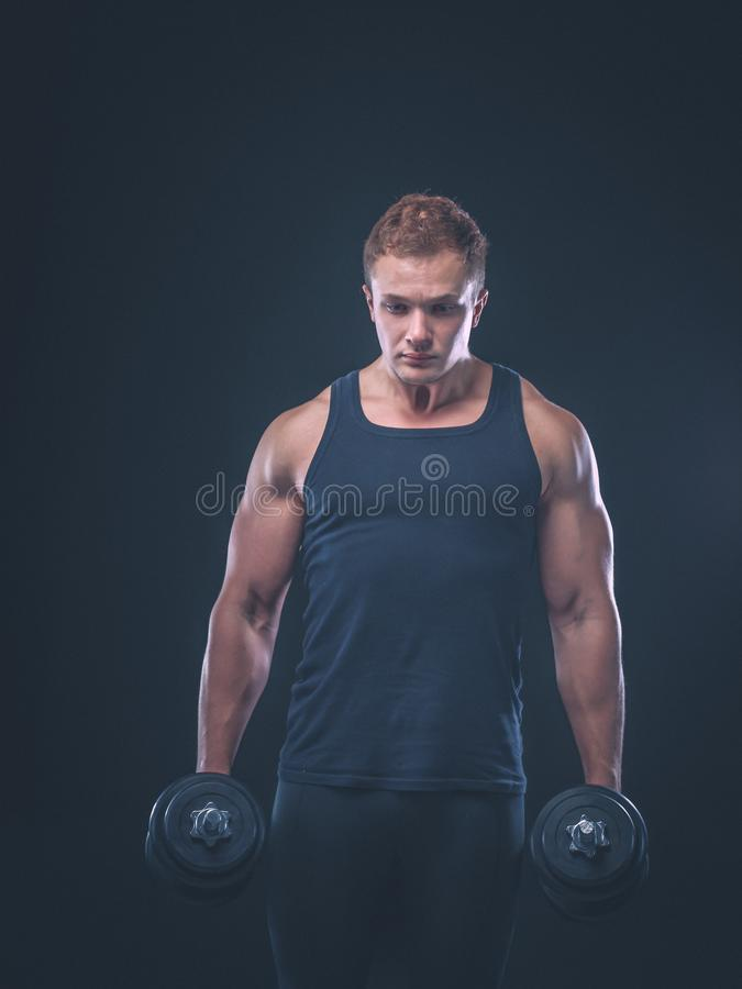 Przystojny mięśniowy mężczyzna pracujący z dumbbells out obrazy stock