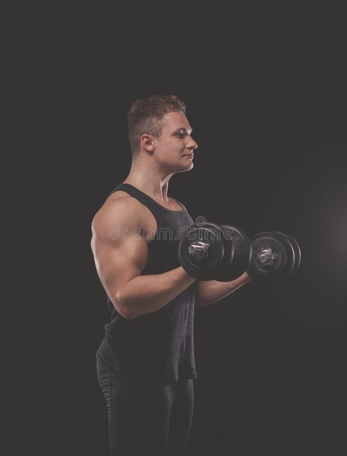 Przystojny mięśniowy mężczyzna pracujący z dumbbells out obraz stock