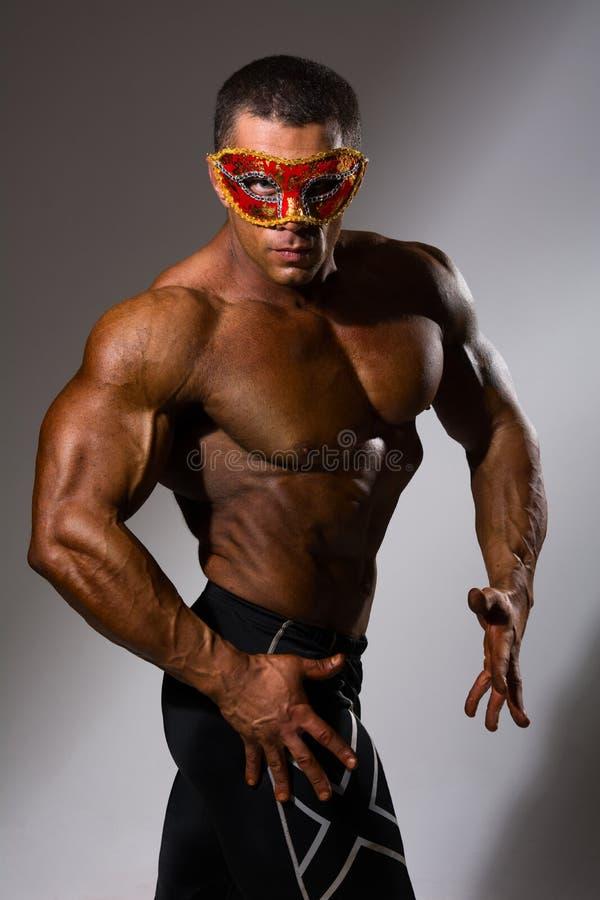 Przystojny, mięśniowy mężczyzna w maskaradowej masce, fotografia royalty free