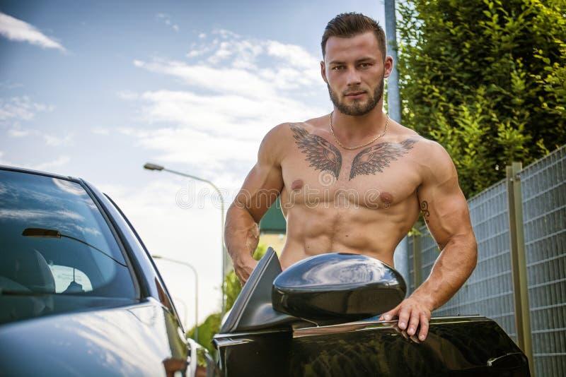Przystojny mięśniowy mężczyzna z tatuażami dostaje w samochodzie obraz stock