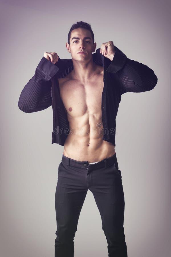 Przystojny mięśniowy młody człowiek bierze daleko koszula fotografia royalty free