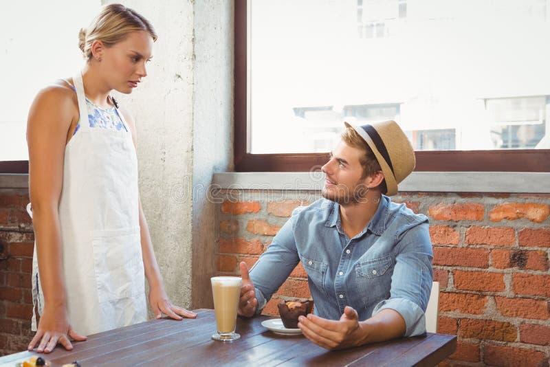 Przystojny modniś opowiada blondynki kelnerka obraz royalty free