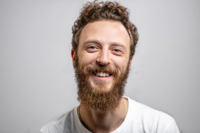 Przystojny modnisia mężczyzna ono uśmiecha się przy kamerą nad białym tłem z brodą fotografia stock
