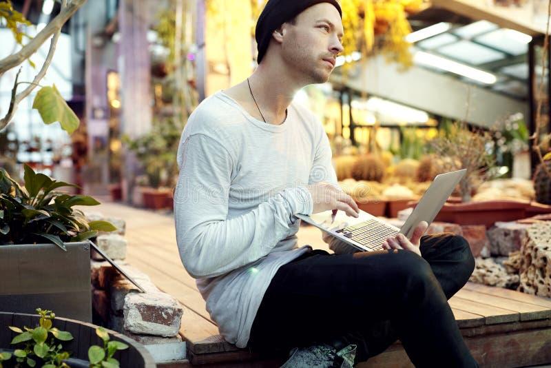 Przystojny modnisia mężczyzna portret marzy o uruchomienie projekcie, pracuje na przenośnym laptopie Facet w czarnego kapeluszu p obraz royalty free