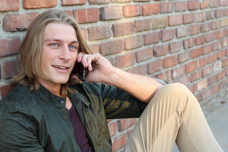 Przystojny modnisia młody człowiek siedzi outdoors i opowiada na telefonie komórkowym z długim blondynem obraz royalty free