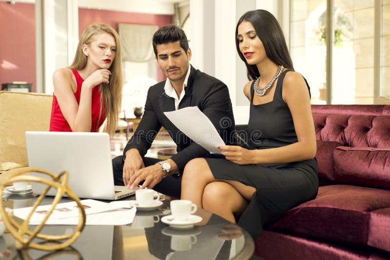 Przystojny modny mężczyzna z dwa powabnymi kobietami w biznesowym spotkaniu fotografia royalty free