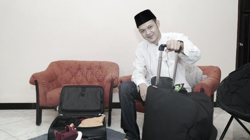 Przystojny muzu?ma?ski azjatykci m??czyzna z traditonal songkok lub kierownicza nakr?tka przygotowywamy walizka baga? dla eid Mub obraz stock