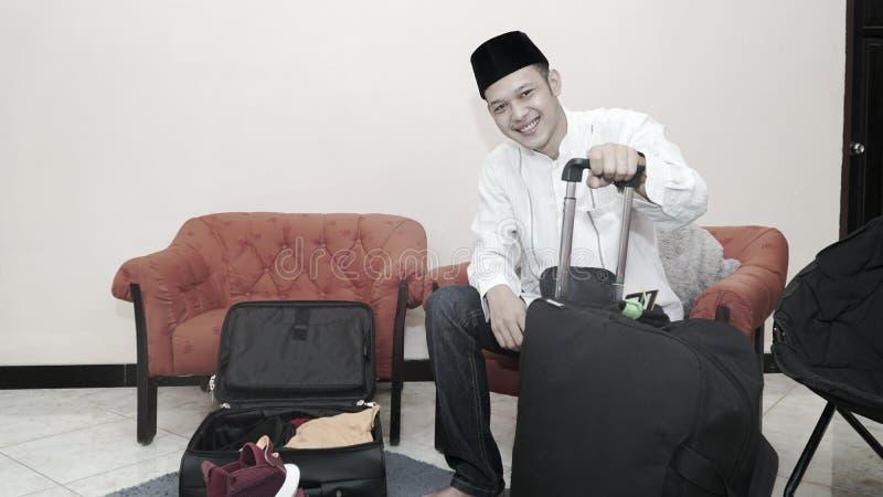 Przystojny muzu?ma?ski azjatykci m??czyzna z traditonal songkok lub kierownicza nakr?tka przygotowywamy walizka baga? dla eid Mub zdjęcie stock