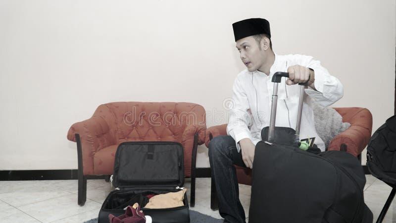 Przystojny muzu?ma?ski azjatykci m??czyzna z traditonal songkok lub kierownicza nakr?tka przygotowywamy walizka baga? dla eid Mub zdjęcia stock