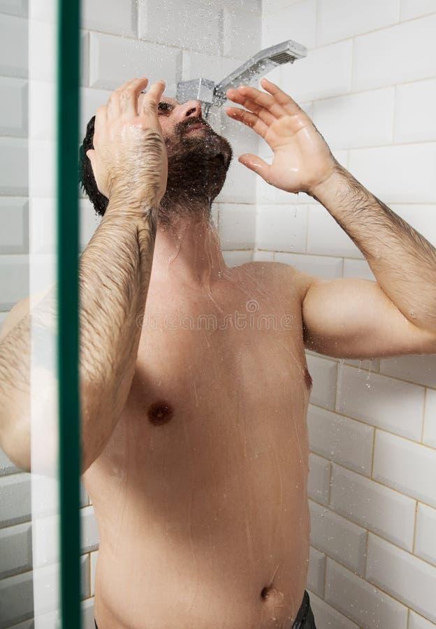 Przystojny nagi młody człowiek bierze prysznic w łazience zdjęcia stock
