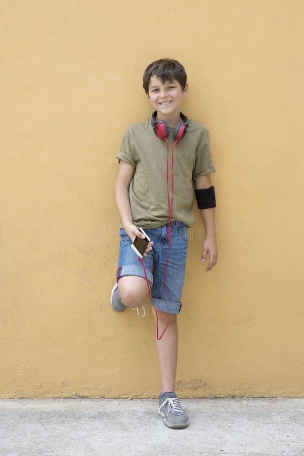 Przystojny nastoletni będący ubranym zieloną koszulkę słucha muzyka obraz stock