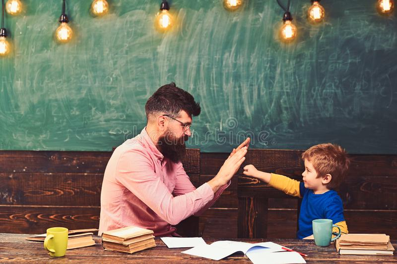 Przystojny nauczyciel i śliczny dzieciak bawić się w sala lekcyjnej Uczeń dokonuje zadanie Mały mistrza witanie obraz stock