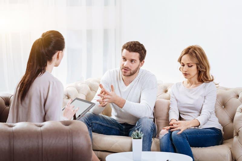 Przystojny nieszczęśliwy mężczyzna obsiadanie z jego żoną na kanapie obraz stock