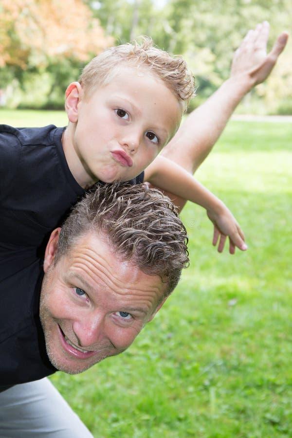 Przystojny ojca piggyback z młodej syna dziecka chłopiec domu plenerowym ogródem zdjęcia royalty free