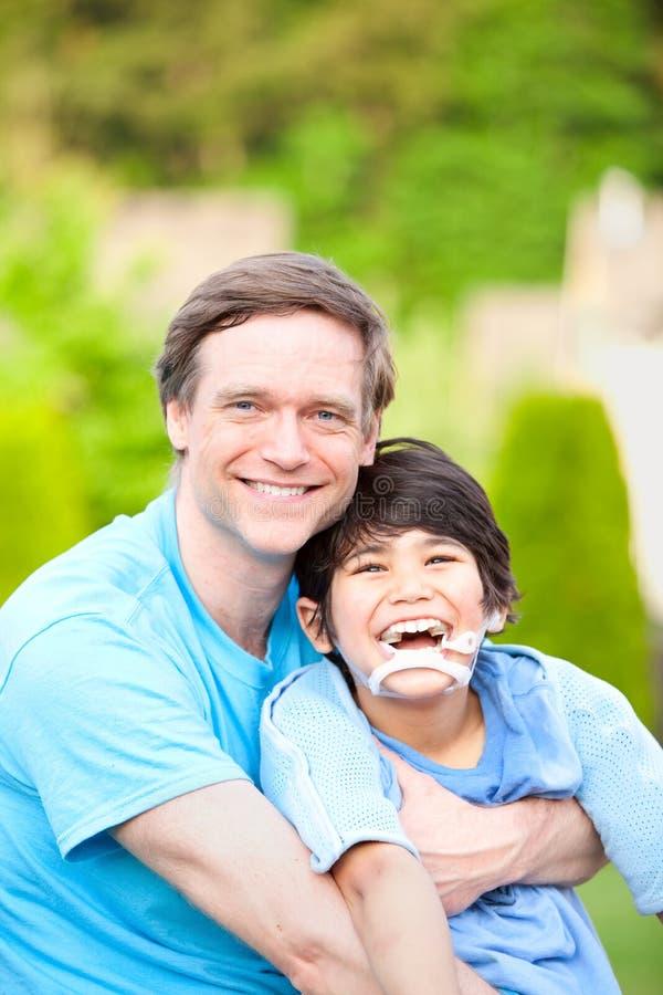 Przystojny ojciec trzyma uśmiechać się niepełnosprawnego syna outdoors zdjęcia royalty free
