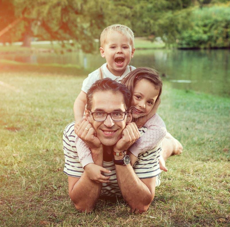 Przystojny ojciec z jego ukochanymi dziećmi odpoczywa w parku obraz stock