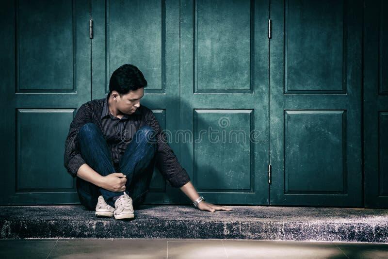 przystojny osamotniony mężczyzna siedzi samotnie na th w sfrustowanej depresji zdjęcie stock
