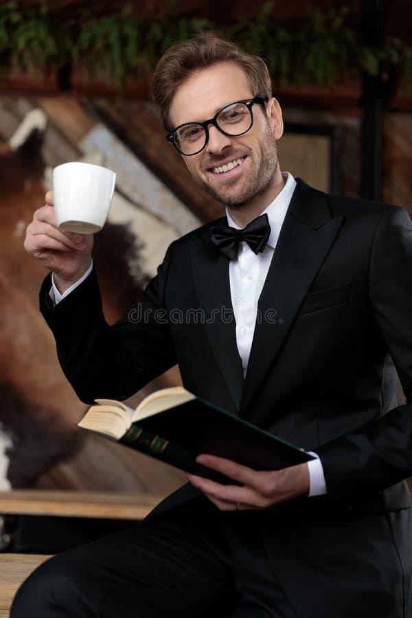 Przystojny pan młody, trzymający filiżankę kawy zdjęcia stock
