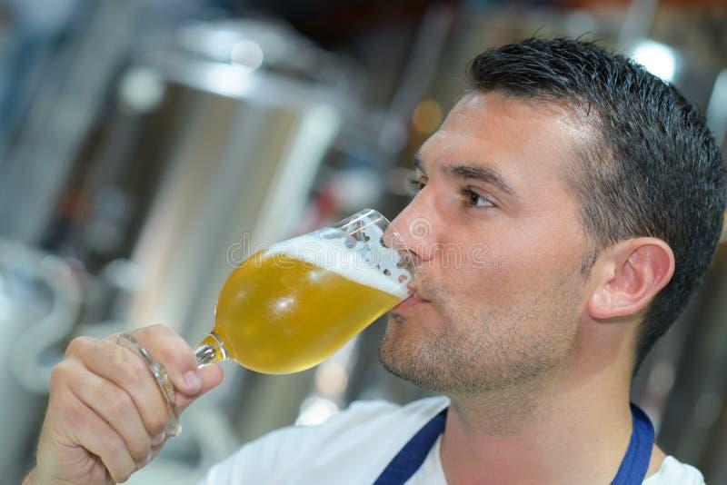 Przystojny piwowar w jednolitym smacznym piwie przy browarem obraz stock