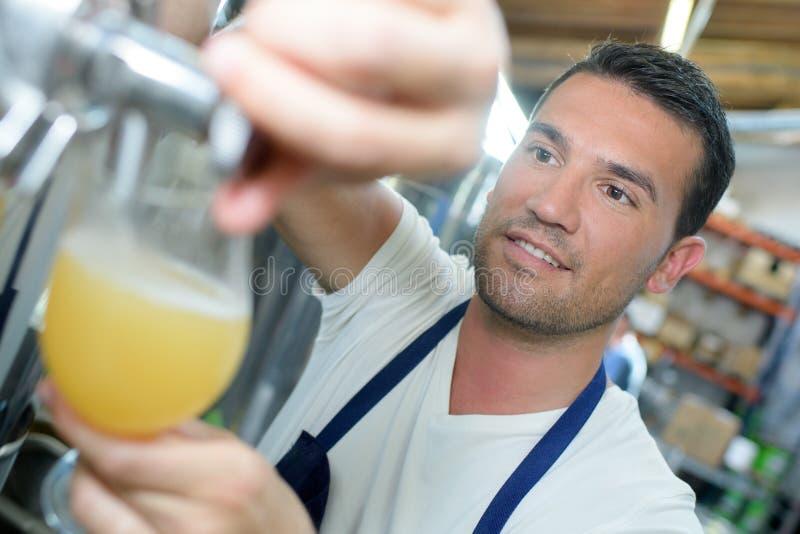 Przystojny piwowar w jednolitym smacznym piwie przy browarem zdjęcia royalty free