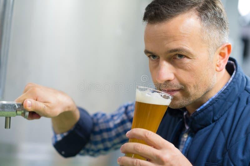 Przystojny piwowar w jednolitym smacznym piwie przy browarem obraz royalty free