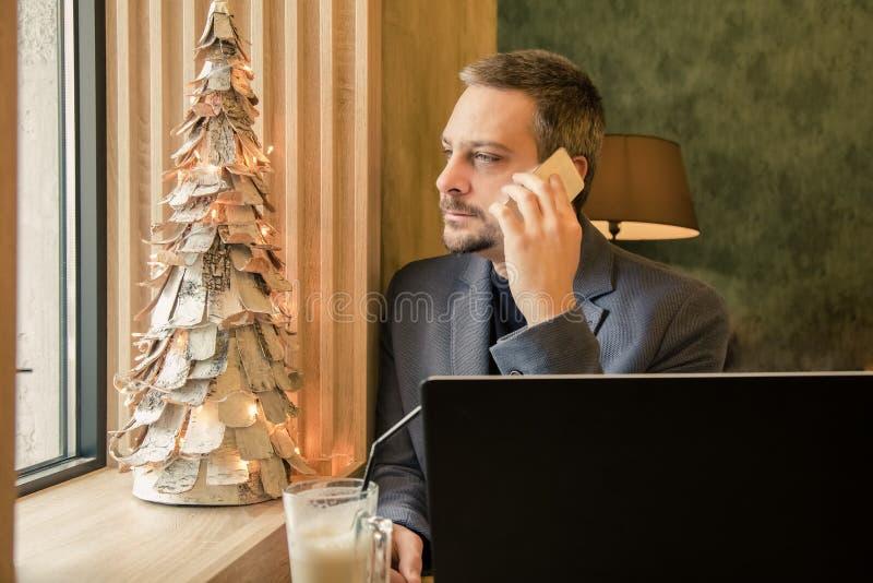 Przystojny pomyślny biznesmen opowiada na telefonie komórkowym, używać l fotografia stock