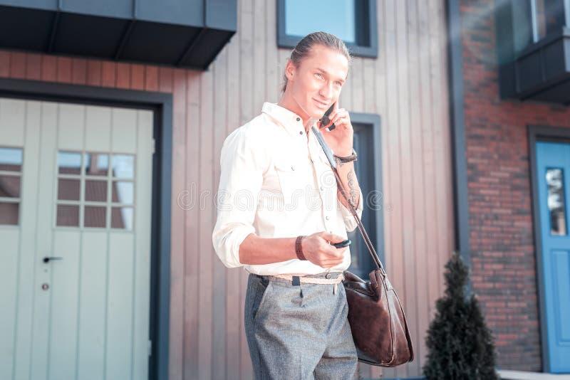 Przystojny pomyślny biznesmen otwiera jego samochód podczas gdy trzymający klucz obrazy stock