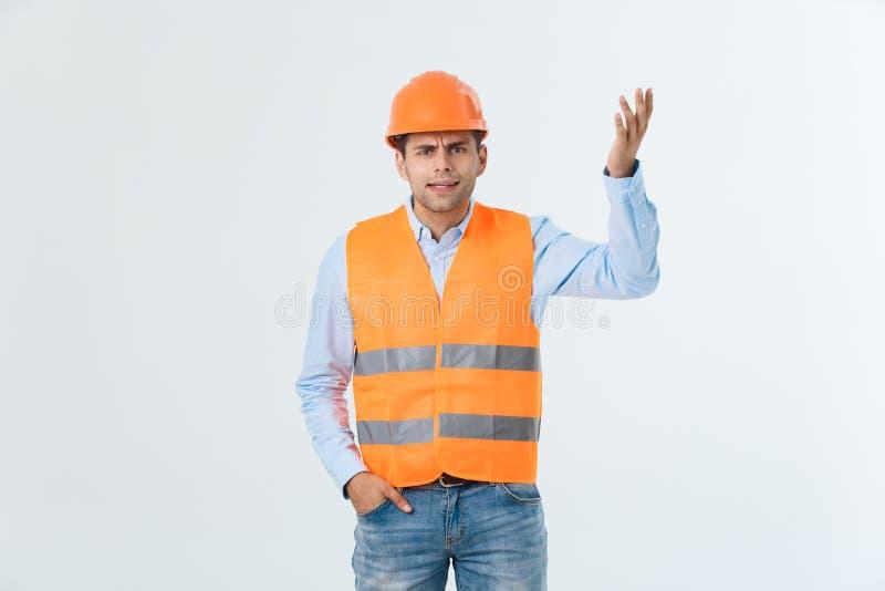 Przystojny potomstwo inżyniera mężczyzna jest ubranym zbawczego hełm z poważną twarzą i ręką nad białym tłem szokował z wstydem zdjęcie royalty free