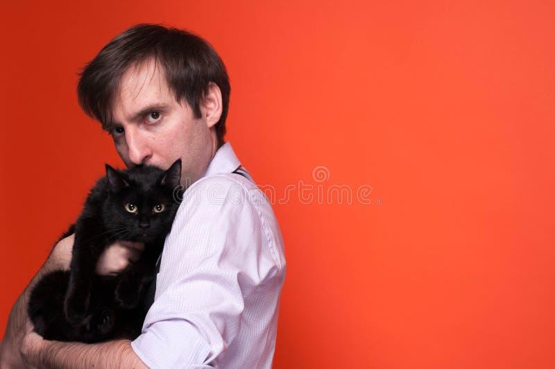 Przystojny poważny mężczyzna, patrzeje kamerę, mienia i całowanie czarnego kota, fotografia royalty free