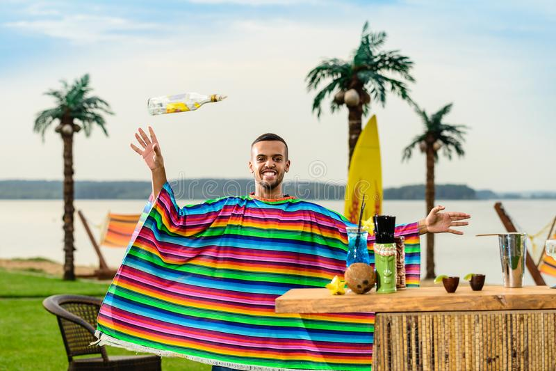 Przystojny pozytywny Meksykański barman w kolorowym poncho rzuca up fotografia royalty free