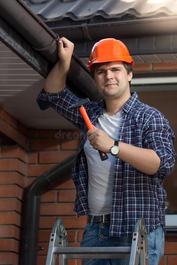 Przystojny pracownik w hardhat pozuje z młotem na krok drabinie fotografia royalty free