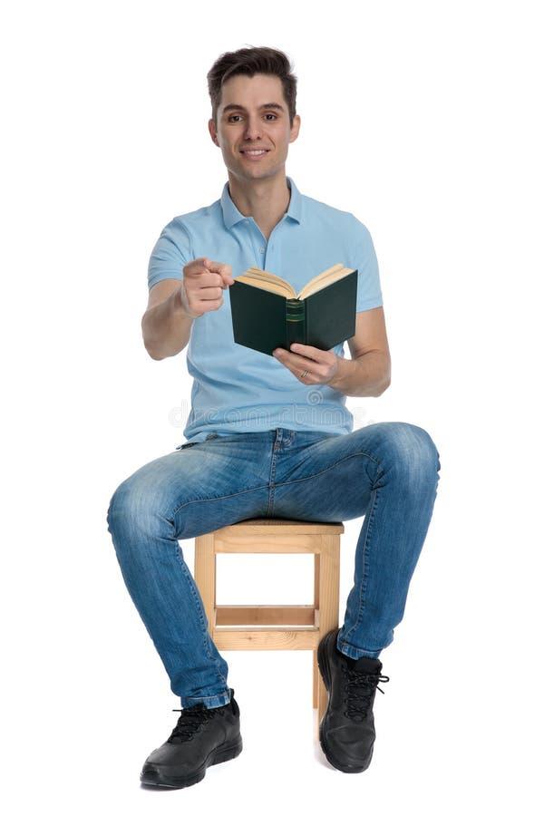 Przystojny przypadkowy mężczyzna wskazuje książkę i trzyma fotografia royalty free