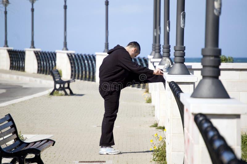 przystojny robi mężczyzna rozciąganie plenerowy biel zdjęcie stock