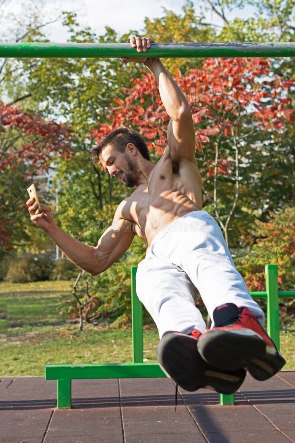Przystojny samiec Jeden ręki ciągnienie W górę treningu i Smat telefonu Używać Uliczni treningów ćwiczenia fotografia stock