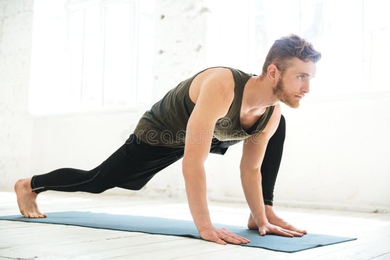 Przystojny skoncentrowany mężczyzna robi joga na macie zdjęcie stock