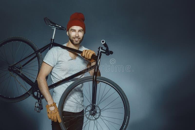Przystojny sporta napadu mężczyzna mienia bicykl Przystojny mężczyzna z bicycl zdjęcie stock