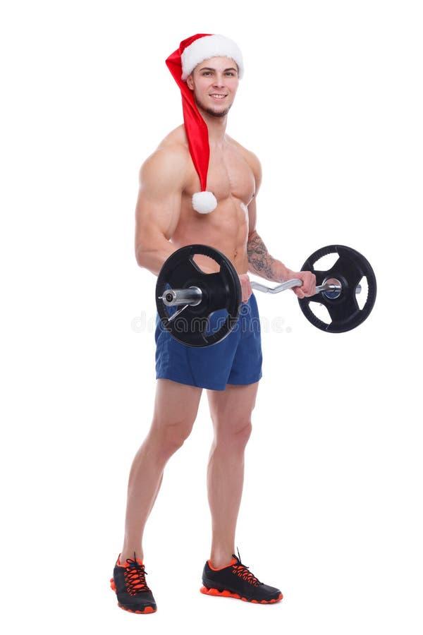 Przystojny sportowy facet z nagą półpostacią i Santa kapeluszem, pompy jego bicepsy z barbell zdjęcie stock