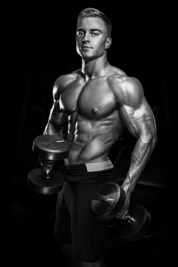 Przystojny sportowy faceta trening z dumbbells obraz royalty free