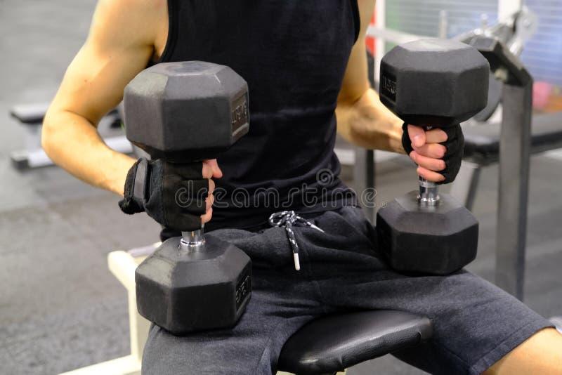 Przystojny sportowy mężczyzna trenuje jego ramiona z dumbbells siedzi na ławce w gym obraz stock
