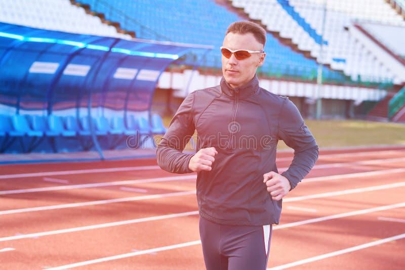 Przystojny sportowy mężczyzna bieg na kieratowym stadium obrazy stock