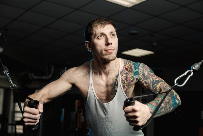 Przystojny sportowy mężczyzna trenuje piersiowych mięśnie na blokowym symulancie w gym obraz royalty free