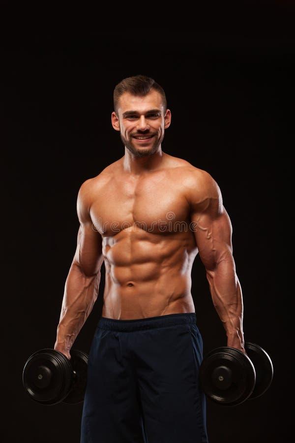 Przystojny sportowy mężczyzna w gym pompuje up mięśnie z dumbbells w gym Sprawności fizycznej mięśniowy ciało odizolowywający na  zdjęcia royalty free