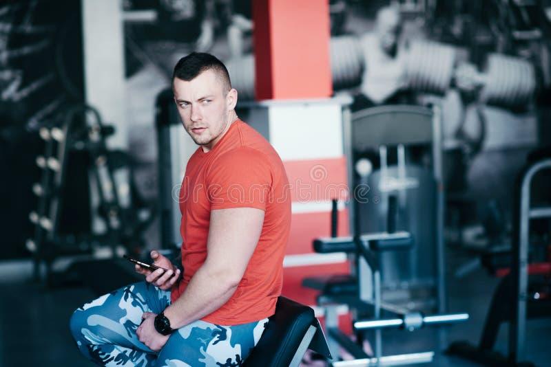 Przystojny sportowy mężczyzna w gym, use telefon komórkowy, surfuje interneta socjalny sieć fotografia stock