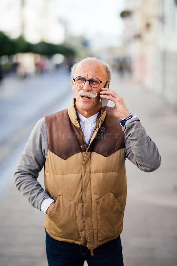 Przystojny starszego mężczyzna mienia telefon komórkowy podczas gdy stojący na ulicie zdjęcia stock