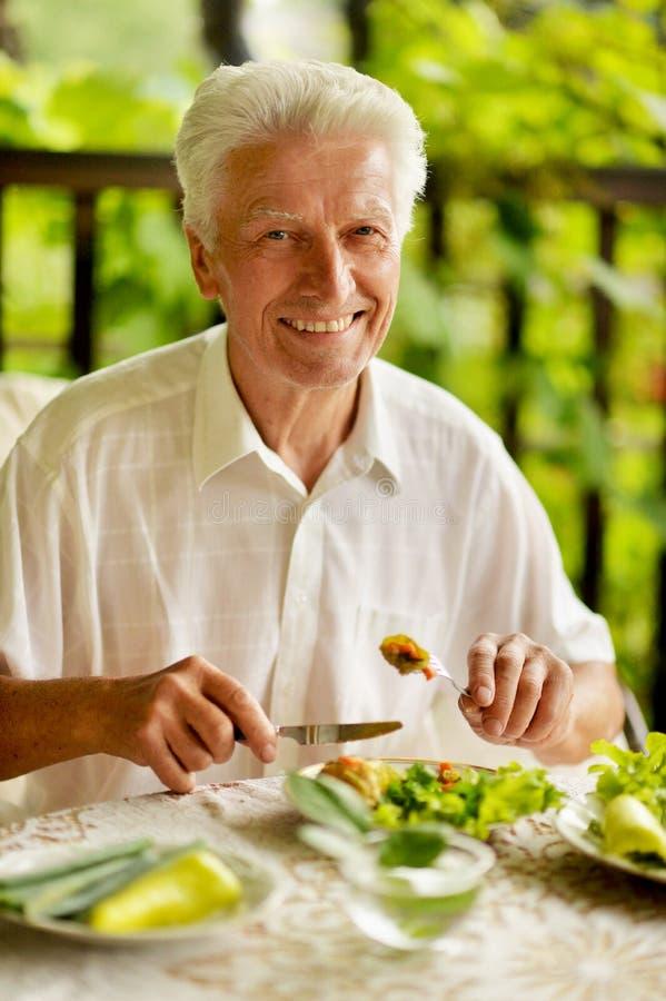 Przystojny starszy mężczyzna je zdrowego śniadanie outdoors obraz stock