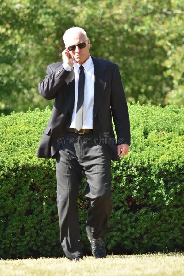 Przystojny starszy rangą ochroniarz strażnika słuchanie Jest ubranym okularów przeciwsłonecznych Chodzić fotografia royalty free