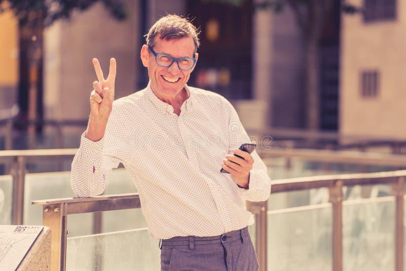 Przystojny szczęśliwy mężczyzna w jego 60s dosłaniu i odbiorcze wiadomości tekstowe na jego telefonie komórkowym w starym człowie obrazy royalty free