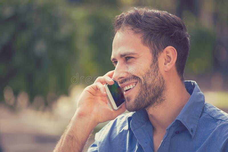 Przystojny szczęśliwy uśmiechnięty miastowy fachowy mężczyzna używa opowiadać na mądrze telefonie fotografia royalty free